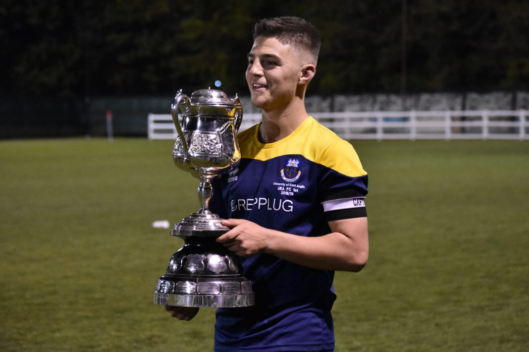 UEA FC Captain Ben George lifts the Mummery Cup